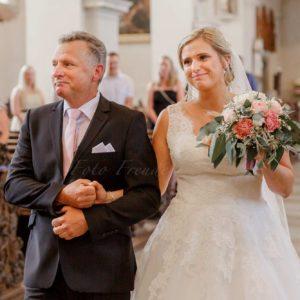 brautvater bringt braut in wunderschoenem brautkleid bei der kirchlichen trauung zum altar in bamberg von hochzeitsfotograf