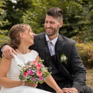 lachendes ehepaar am hochzeitstag in der natur bei hochzeitsshooting