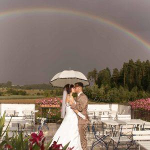 hochzeitsfotografin zeigt hochzeitsbilder für reportage mit regenbogen und schirm in bamberg