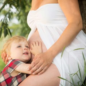 babybauchshooting schwangere vor baum mit geschwisterchen schwester kopf am bauch im sommer am baum in forchheim